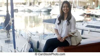 Woman Relaxing On Bench In Yacht Port - Young attractive...