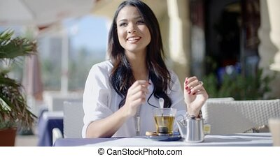 Girl Sitting At Cafe With Cup Of Tea - Young woman stirring...