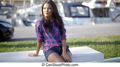 Young Woman Sitting On Bench In Harbor - Young female...