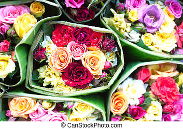 Multicolored roses wrapped in banana leaves natural...