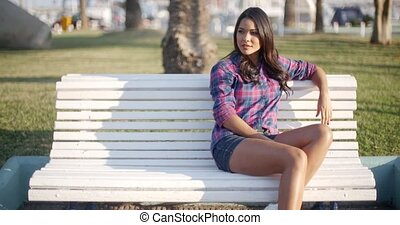Girl Relaxing On Bench In Park - Happy young woman relaxing...