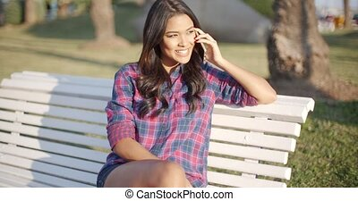 Woman Using Cell Phone On Park Bench - Young woman using...