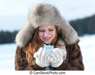 portrait of girl with gift at winter scene and snow in...