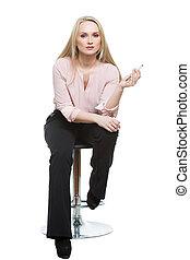 Elegant beautiful woman sitting on a contemporary metal bar...