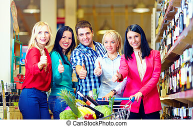 group of happy people in supermarket, thumb up