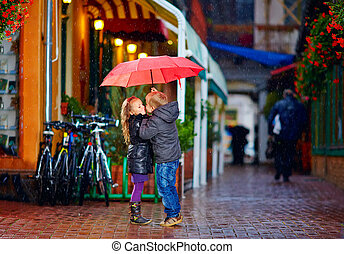 young couple kissing under the umbrella on the street