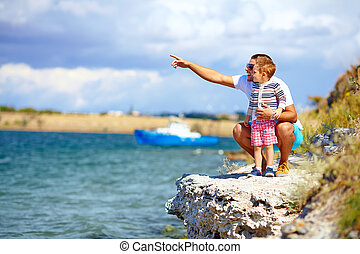 happy father and son on the cliff near the lake