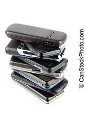 Heap of modern mobile phones on white