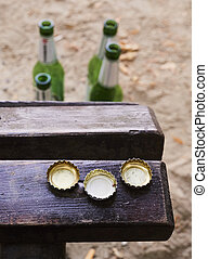 Beer bottles on benches in park - Beer bottles on benches in...