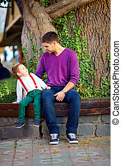 father and son having fun on the bench in park