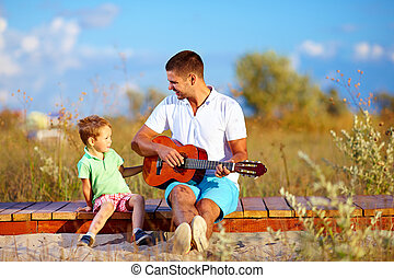 portrait of cute boy playing a guitar on summer field