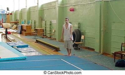 Gymnast doing backflip. Slow motion. - Gymnast doing...