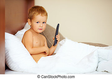 cute kid with remote in bed room