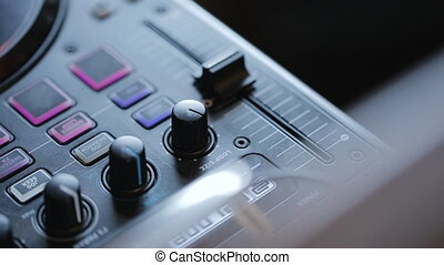 remote control sound with buttons, knobs, levels for a music DJ at a public event.