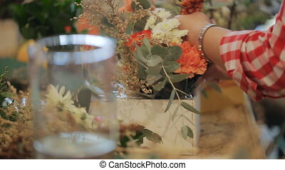 Senior expert of the master florist working with flowers, bouquets, boutonnieres, herbs, plants