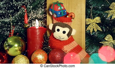 Christmas background with candle lights and gifts on red sock with monkey.