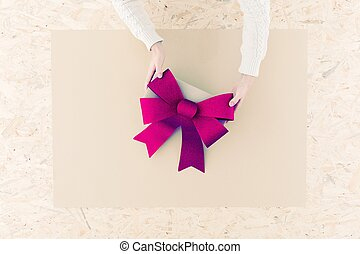Pink bow on table - Female hands holding big bow on table