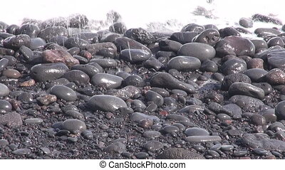 Wet pebbles with crashing waves - Wet black round pebbles...