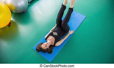 Fit Woman Stretching Legs Indoors - This is a shot from...