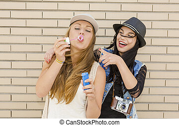 Playing with soap bubbles - Teenage firends playing with...