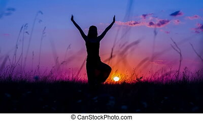 Silhouette of a Young Girl Doing Yoga Tree Pose At Sunset -...