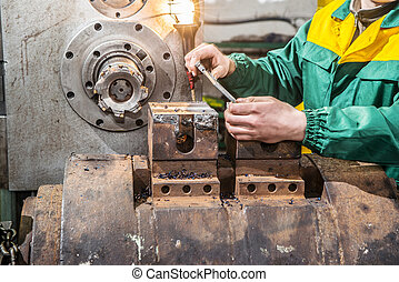 Factory worker measure detail with digital caliper micrometer during finishing metal working on lathe grinder machine