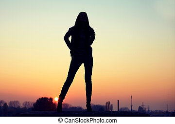 silhouette of seductive woman on  rooftop at urban sunset