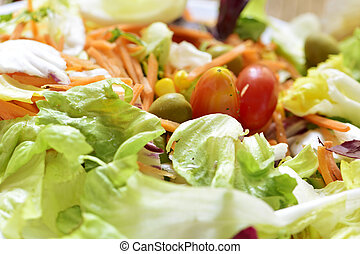 green salad with carrot, olives, cherry tomatoes and sweet...