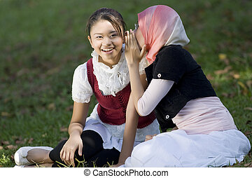 two girl whisper together in the garden
