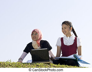 two girls studying together in the field