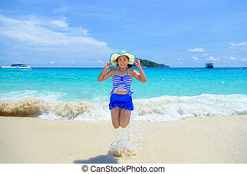 Woman jumping with happy on the beach at Thailand