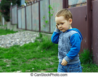 cute baby boy emulate talking on the phone, while playing...