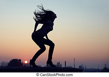 silhouette of slim seductive woman standing on  rooftop at sunset. urban background