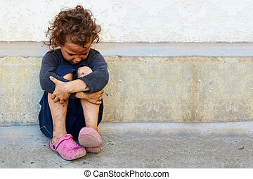 poor, sad little child girl sitting against the concrete...