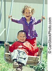 poor but happy little gypsy siblings in swing outdoor