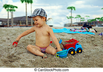 cute baby boy playing with toys on beach