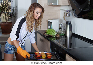 girl with baked cupcakes in her kitchen,  beautiful young woman gets out of  oven muffins