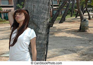 young lady get posed beside coconut tree - young asian lady...