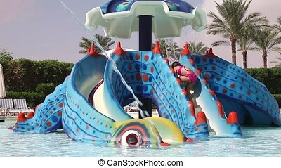 Little girl riding on a water slide - Little girl has fun...