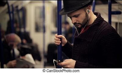 Man listening music on a tube train standing