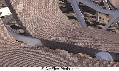 Lounges with beach umbrellas on brown sand by the town by...