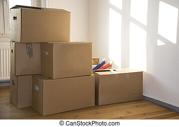 house moving - stacked moving boxes in a room with sun light