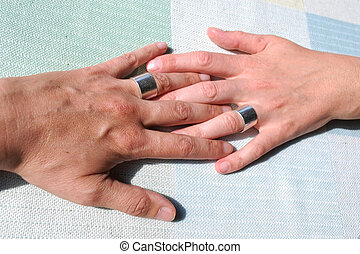 gay couple - hand of two gay people in the sunlight
