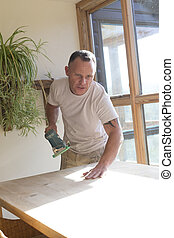 Joiner using a sander on a table surface - Wood joiner using...