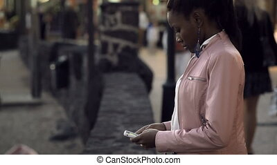 Black girl texts messages on the phone