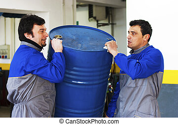 Workers with drum - Two industrial workers with a barrel