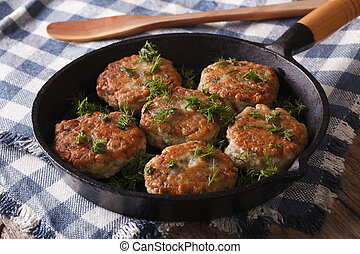fishcakes with herbs close-up in a pan Horizontal -...