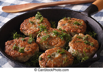 Cooking fish cakes with herbs close-up in a pan Horizontal -...