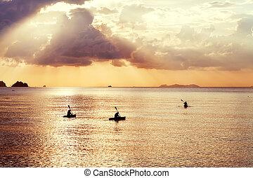 three kayak float at sunset
