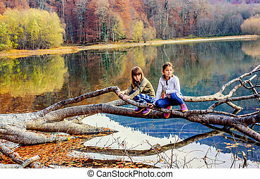 Two little girls sitting on the tree on Lake Biogad...